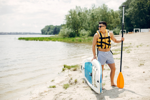 Handsome man with a sup. Surfer in a yellow vest.